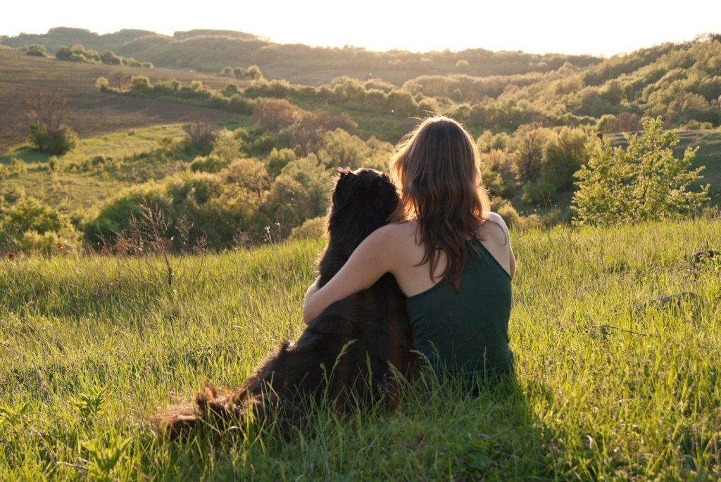 A beautiful young woman hugs her dog as they sit in a field